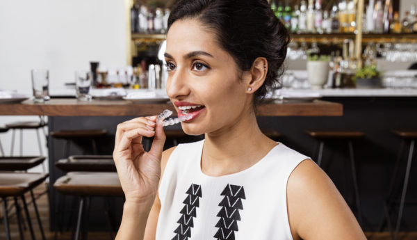 Woman putting in a removable clear retainer.
